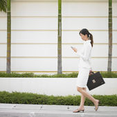 Businesswoman walking with cell phone and briefcase — Stock Photo