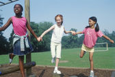 Three girls playing in park while holding hands — Stock Photo