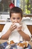 Hispanic boy eating homemade cupcake — Stock Photo