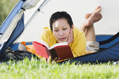 Woman reading in a tent — Stock Photo