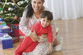 Mom sitting in front of Christmas tree holding her young son — Stock Photo
