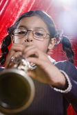 Hispanic girl playing clarinet — Stock Photo