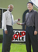 Man handing the keys to a new house to owner — Stock Photo