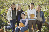 Group of girls in pumpkin patch — Stock Photo