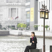 Businesswoman talking on cell phone outdoors — Stock Photo