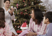 Hispanic father video recording family on Christmas — Stock Photo