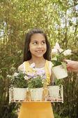 Hispanic girl holding potted flowers outdoors — Stock Photo