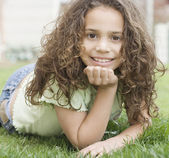 Young girl laying in grass — Stock Photo