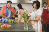 Two middle-aged couples in kitchen — Stock Photo