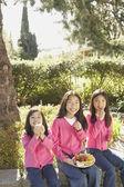 Tre unga asiatiska systrar äta utomhus — Stockfoto