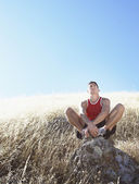 Man resting on hillside rock — Stock Photo