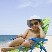 Hispanic boy sitting in beach chair — Stock Photo