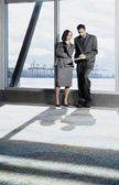 Two businesspeople talking near window — Stockfoto
