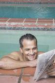 Hispanic man reading newspaper in swimming pool — Stock Photo