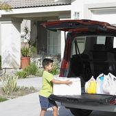 Boy carrying groceries from van — Stock Photo