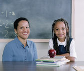 Teacher and school girl smiling for the camera — Stock Photo