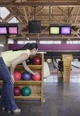 Woman picking bowling ball — Zdjęcie stockowe