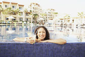 Hispanic woman with drink leaning on pool edge — Stock Photo