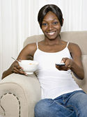 African woman eating cereal and changing channel with remote control — Stock Photo