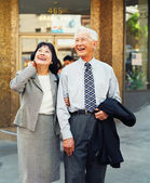 Senior couple laughing and walking in urban setting — Stock Photo