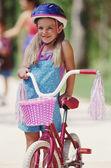 Ung flicka håller cykel med tofsar och korg — Stockfoto