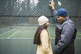 Couple talking by tennis court — Stock Photo