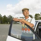 старший азиатских человек, опираясь на двери автомобиля — Стоковое фото