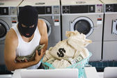 Man in ski mask with bags of money at laundromat — Stock Photo