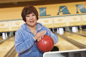 Woman with bowling ball at bowling alley — Stock Photo