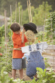 Young Hispanic boy putting hat on scarecrow — Stock Photo
