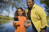 Africká matka a dcera při pohledu na fotografii venku — Stock fotografie