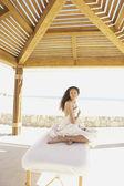 Kvinna sitter på massagebänk utomhus — Stockfoto