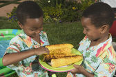 Two young boys sharing grilled corn — Stock Photo
