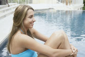 Young woman sitting at poolside — Stock Photo