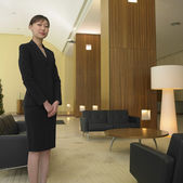 Asian businesswoman standing in lobby — Stock Photo