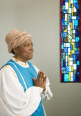 African woman wearing church choir gown and praying — Stock Photo