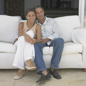 Couple sitting on sofa — Stock fotografie