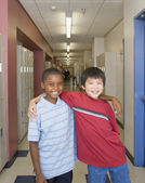 Young boys smiling in school hallway — Stock Photo