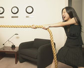 Businesswoman pulling rope in office — Stock Photo