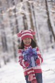 Young Asian girl holding gift in snow outdoors — Stock Photo