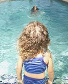 年轻姑娘坐在游泳池的边缘 — 图库照片