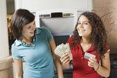 Multi-ethnic teenage girls holding money and credit card — Stock Photo