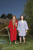 Couple in robes watering yard — Stock Photo