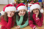 Portrait of three girls with Santa hats in front of Christmas tree — Stock Photo