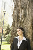 Hispanic businesswoman leaning on tree listening to music — Stock Photo