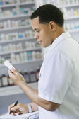 African American male pharmacist with prescription bottle — Stock Photo