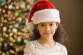 Hispanic girl wearing santa hat — Stock Photo