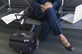 Low section of businesswoman with luggage and laptop — Stock Photo