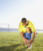 Soccer player tying shoe — Stock Photo