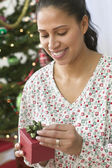 Woman opening gift in front of Christmas tree — Stok fotoğraf